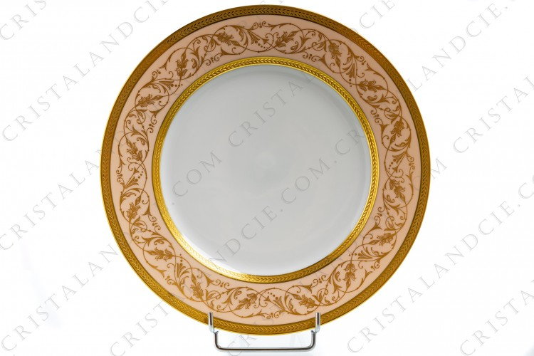 Dinner plate in Limoges china by Lafarge decorated with two gold inlays friezes of laurels and with gold arabesques of foliage on a pale pink background