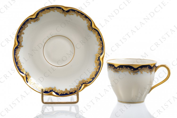 Coffee cup in china of Limoges by Theodore Haviland decorated with cobalt blue and gold stripes and with a gold frieze of ribbons and leaves