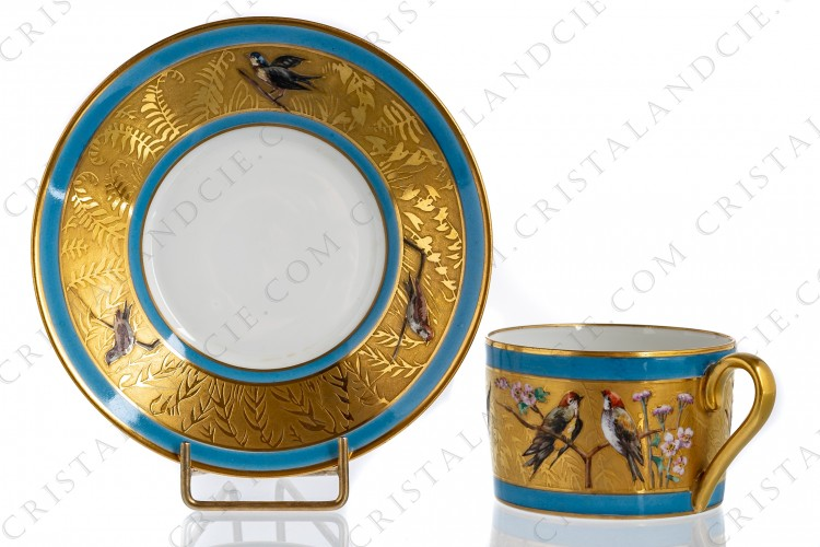 Tea cup in Limoges china decorated with hand-enameled birds and flowers on a background in gold inlays surrounded by blue enameled borders photo-1