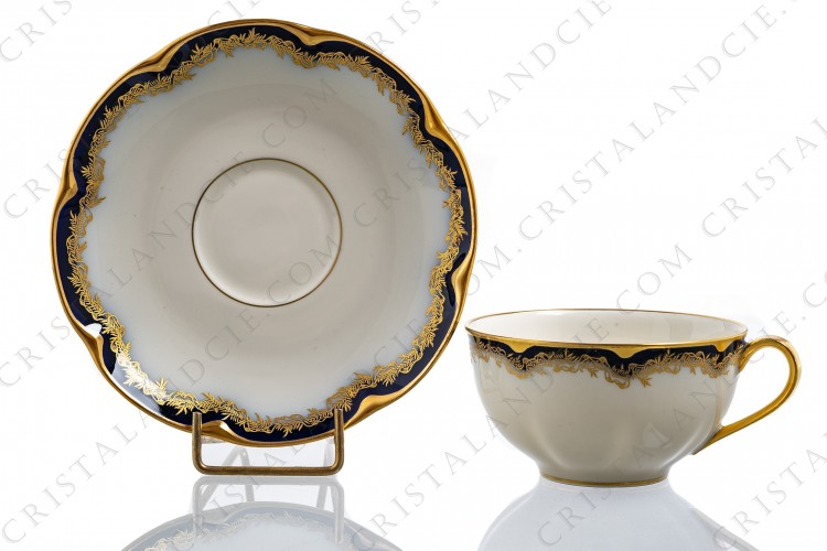 Tea cup in china of Limoges by Theodore Haviland decorated with cobalt blue and gold stripes and with a gold frieze of ribbons and leaves